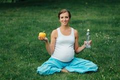 Schwangere Yogafrau mit einer Flasche Wasser und grünem Pfeffer, im Lotussitz Park, Gras im Freien, Wald Lizenzfreie Stockfotos