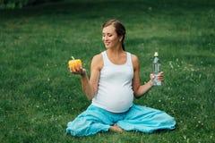 Schwangere Yogafrau mit einer Flasche Wasser und grünem Pfeffer, im Lotussitz Park, Gras im Freien, Wald Stockfotos