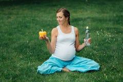 Schwangere Yogafrau mit einer Flasche Wasser und grünem Pfeffer, im Lotussitz Park, Gras im Freien, Wald Stockfoto