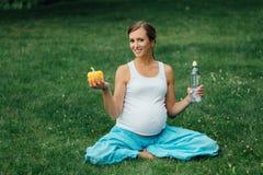 Schwangere Yogafrau mit einer Flasche Wasser und grünem Pfeffer, im Lotussitz Park, Gras im Freien, Wald Lizenzfreies Stockfoto