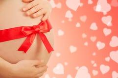 Schwangerer Bauch der Frau mit rotem Farbband Stockfoto