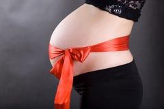 Schwangerer Bauch mit einem Bogen Stockfotografie