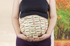Schwangerer Bauch mit Hilfetext Lizenzfreies Stockfoto