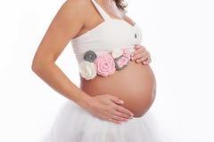 Schwangerer Bauch mit rosa gewirkter Schärpe Stockfotografie