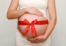 Schwangerer Bauch mit rotem Farbband Stockfotografie