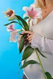 Schwangerer Bauch und Lilie Stockbild