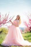Schwangerer glücklicher Rosagarten der Frau im Frühjahr Lizenzfreie Stockbilder