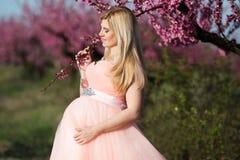 Schwangerer glücklicher Rosagarten des Mädchens im Frühjahr Lizenzfreie Stockfotografie