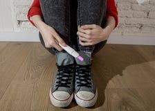 Schwangeres Jugendlichmädchen oder junge hoffnungslose Frau, die positiven rosa Schwangerschaftstest halten Stockfoto