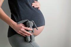 Schwangeres Mädchen, das ein Spielzeugkaninchen hält Lizenzfreies Stockfoto