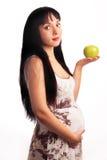 Schwangeres Mädchen der Junge isst einen Apfel. Lizenzfreie Stockfotografie