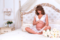 Schwangeres Mädchen der Rothaarigen sitzt auf Bett im Lotussitz, der Bauch umarmt Stockbild
