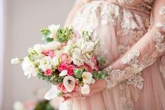 Schwangeres Mädchen in einem beige Kleid mit einem Blumenstrauß in den Händen frech Warten auf ein Wunder Lizenzfreie Stockbilder