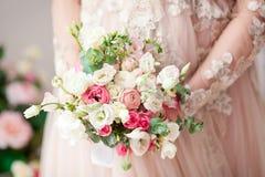 Schwangeres Mädchen in einem beige Kleid mit einem Blumenstrauß in den Händen frech Warten auf ein Wunder Lizenzfreie Stockfotografie