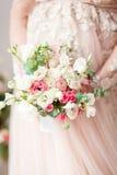 Schwangeres Mädchen in einem beige Kleid mit einem Blumenstrauß in den Händen frech Warten auf ein Wunder Stockfotografie