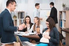 Schwangeres Mädchen im Büro trinkt Kaffee mit Leiter im Büro Schwanger mit Kollegen stockfotografie
