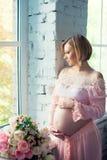Schwangeres Mädchen nahe dem Fenster, das Bauch umarmt Glückliche 9 Monate der Schwangerschaft und des Wartebabys Stockfotografie