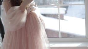 Schwangeres Mädchen sitzt nahe einem Fenster in einem schönen rosa Kleid stock footage