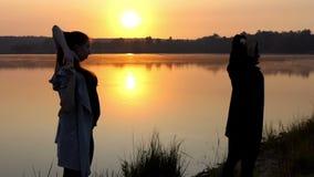 Schwangeres Mädchen tut eine Yoga-Übung mit ihrem Trainer auf einem See bei Sonnenuntergang in Slo-MO stock footage