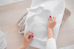 Schwangeres M?dchen faltet Babykleidung in einem Stapel Die Verantwortung der Frauen zu Hause Faltende Kleidung lizenzfreies stockbild