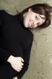 Schwangeres Mädchen, das auf dem Sofa liegt Stockfotos