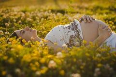 Schwangeres sich hinlegen der recht jungen Frau Stockbilder