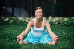 Schwangeres Yoga im Lotussitz auf dem Waldhintergrund im Park das Gras, im Freien, Gesundheitsfrau Stockfoto