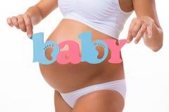 """Schwangerschaft mutterschaft Blaues und rosa Wort """"BabyÂ"""" nahe dem schwangeren Bauch Lizenzfreie Stockfotos"""