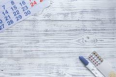 Schwangerschafts-Planung Kalender, empfängnisverhütende Pillen, Schwangerschaftstest auf hölzernem copyspace Draufsicht des Hinte stockbilder