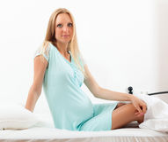 Schwangerschaftsfrau im blauen Nachthemd Stockfotografie