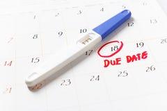 Schwangerschaftstest mit dem positiven Ergebnis, das auf Kalender, Abgabefrist liegt Lizenzfreie Stockfotografie