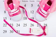 Schwangerschaftstest mit positivem Ergebnis und Babyschuhe auf dem Kalender, erwartend für Baby Stockfoto