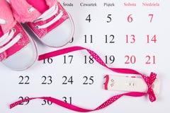 Schwangerschaftstest mit positivem Ergebnis und Babyschuhe auf dem Kalender, erwartend für Baby Lizenzfreies Stockfoto