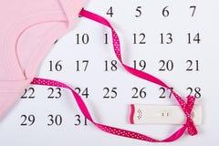 Schwangerschaftstest mit positivem Ergebnis wickelte Band und Bodysuit für neugeborenes auf Kalender ein Stockbild
