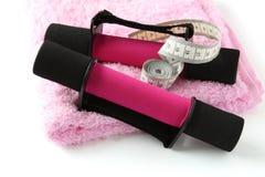 Schwarz-rosa Dumbbell mit Griff und messendem Band auf Tuch Stockfotografie