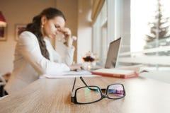 Schwarz umrandete Brille liegt auf Tabelle gegen Hintergrund des Mädchens mit Kopfschmerzen lizenzfreies stockbild