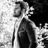 Schwarz-weißes Porträt im Freien des eleganten gutaussehenden Mannes im klassischen der Jacke Naturhintergrund wieder Stockbild