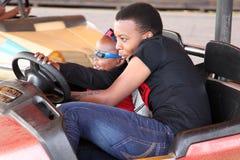 Schwarzafrikanerbruder und -schwester, die Autoskooters genießen Stockfotos
