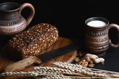 Schwarzbrot der Zusammensetzung auf dem Brett, Weinlesemesser, Milch, Weizen blättert auf dem Tisch und der alte Hintergrund, Kon Lizenzfreies Stockbild