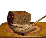Schwarzbrot mit Scheiben und den Ährchen des Weizens Stockfotos