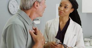 Schwarze Ärztin, die auf die ältere geduldige Atmung hört lizenzfreie stockbilder
