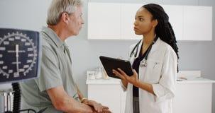 Schwarze Ärztin, welche die Gesundheitsakten des Seniors überprüft lizenzfreies stockbild