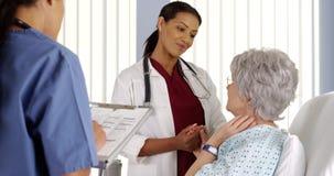 Schwarze Ärztin, welche die Hand des älteren Patienten im Krankenhauszimmer hält Lizenzfreie Stockfotos