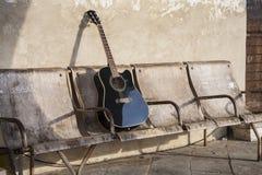 Schwarze Akustikgitarre auf den alten schäbigen Stühlen Stockfotos