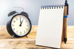 Schwarze alte Uhr und leeres Papier mit Stift, auf Holztisch Lizenzfreie Stockfotografie