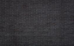 Schwarze Backsteinmauerbeschaffenheit stockfoto