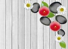 Schwarze Badekurortsteine, -kerzen und -blumen auf weißem hölzernem Stockfoto