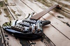 Schwarze Bass-Gitarre auf einem hölzernen Hintergrund Stockfotografie