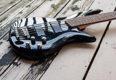 Schwarze Bass-Gitarre auf einem hölzernen Hintergrund Lizenzfreie Stockfotografie