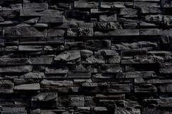 Schwarze Beschaffenheit der Steinwand Hintergrund stockfoto